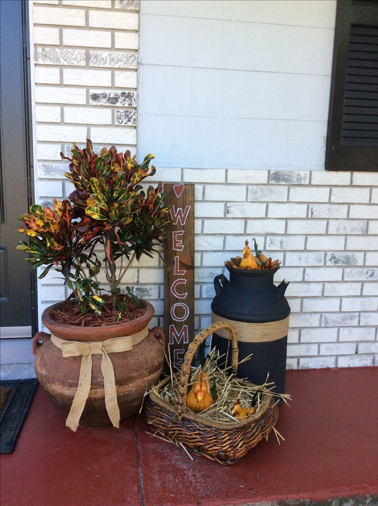 Front porch. Stained concrete floor,painted milk can and wrapped jute twine around can. Added jute ribbon and bow to flower pot and made welcome sign.
