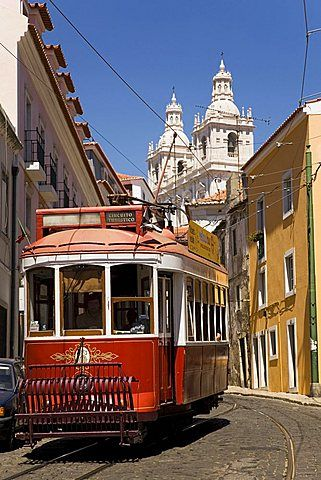 A tram runs along the tourist friendly Number 28 route in Alfama, Lisbon, Portugal...