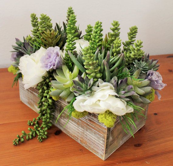 artificial succulent arrangement in a rectangle wood vase