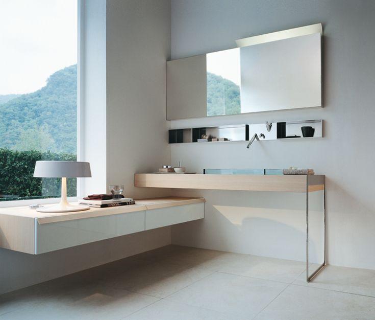 Il piano in rovere chiaro, con lavabo in cristallo LAV002 a semincasso e struttura laterale, si  interseca con i contenitori con maniglie in legno e frontale in Parapan®.
