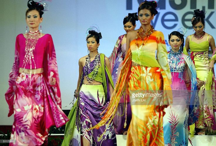 Models display dresses by a local designer at the Fashion week gala night in Kuala Lumpur 15 August 2004. Malaysia's fashion industry is among the top five contributors to the country's exports and the fashion week is aimed to make Malaysia into a regional hub for Asia's textile and fashion scene. AFP PHOTO / Jimin LAI