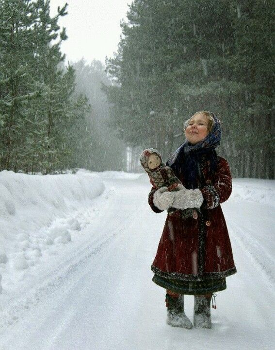 Russian girl with doll in the snow.