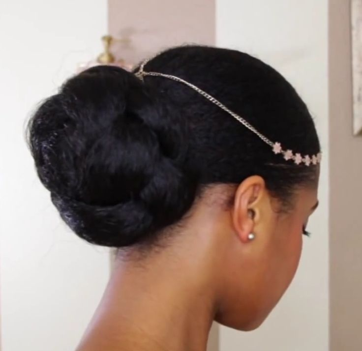 Faux bun created using a pack of kanekalon hair. Put your natural hair into a gelled down bun, braid the kanekalon into a long plait, attach the plait to your real bun using an elastic band, wrap around in a clockwise motion, and use bobby pins to secure it and make sure your real bun stays covered. In gelling down your natural hair, to keep it properly flat, can mix Eco Styler gel and coconut oil,  smooth onto hair gently brush flat, and tie down with a scarf.