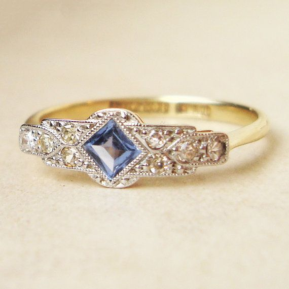 Art Deco Sapphire & Diamond Engagement Ring, Antique Sapphire Platinum and 18k Gold Ring, Approximate Size US 7.25    This amazing ring is c.1920s, a striking, unusual Art Deco design with a wide geometric setting holding a square cut Sapphire and round diamonds. The metal is 18k yellow gold with a Platinum setting. The setting measures 15.8 x 5.7mm, the Sapphire is approx. 3mm, surrounded by eight diamonds approx. 1.4mm each. The band width is approx. 1.8mm, some slight flattening around…