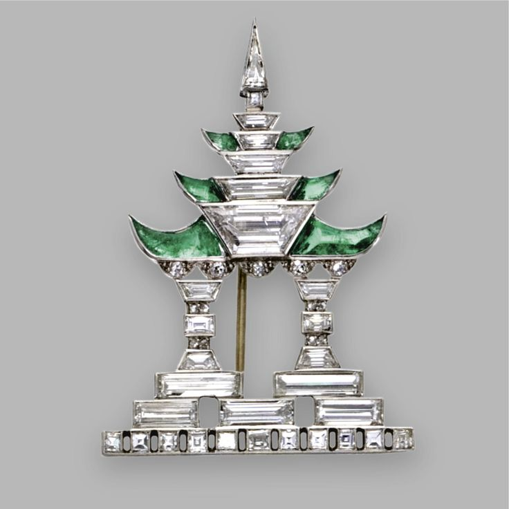 DIAMOND AND EMERALD PAGODA BROOCH, JANESICH, CIRCA 1925. Designed as a pagoda with stylized columns and upturned eaves, set with baguette, square-shaped, trapeze-cut, triangular-shaped, single-cut and rose-cut diamonds weighing approximately 3.00 carats, accented with 6 calibré-cut buff-top emeralds, mounted in platinum, signed JANESICH, numbered 10124.