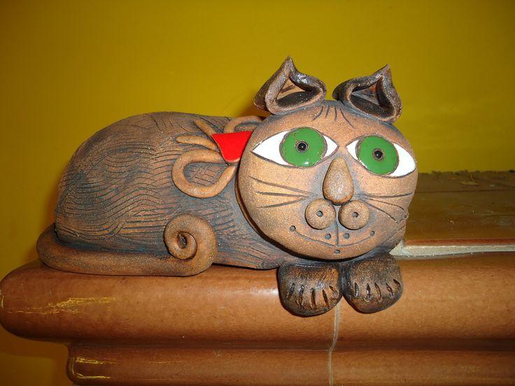 kočka Výrobek je ručně modelovaný ze šamotové hlíny pálený na 1 160stc., detaily jsou domalovány barevnou glazurou. Je vhodný pro vnitřní i venkovní prostory, na trám, parapet...Délka 35cm.