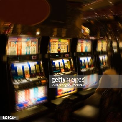 Stock Photo : People in casino, looking at fruit machine