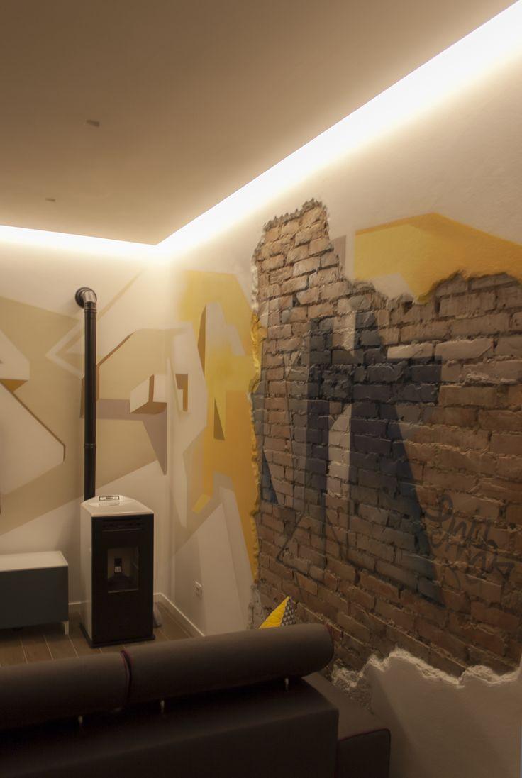 """Un open space ricavato dalla demolizione di tre tramezzature che definivano un bilocale. Lo spazio è caratterizzato da una forte simmetria nella composizione dei volumi e delle illuminazioni artificiali. L'ambiente è contaminato da influenze """"street art"""", come si può notare dal grande graffito che occupa due lati della zona soggiorno e dalla volontà di recuperare l'estetica della parete in mattoni originale."""