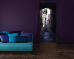 Woonkamer geverfd in opvallende kleuren van paars, blauwgroen en turkoois