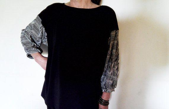 Maglia casacca in jersey nero, con manica in plissè stampato bianco e nero, ripresa da un leggero polsino sotto al gomito