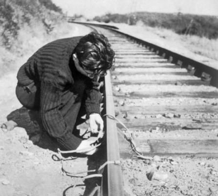 Member of the French resistance setting an explosive charge on a railway line. WW II
