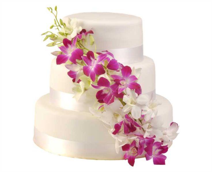 Svatební dort 29 Třípatrový svatební dort, o rozměrech 18 cm, 24 cm a 32 cm, obalen fondánem, dozdoben bílými stuhami a živými květy