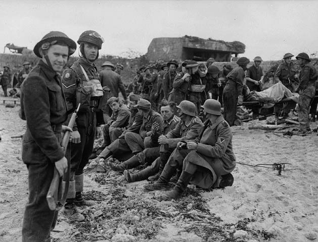 A member of the Canadian Provost Corps (C.P.C.) guarding the first German prisoners to be captured by Canadian soldiers in the Normandy beachhead, France, 6 June 1944. Photographer: Frank L. Dubervill