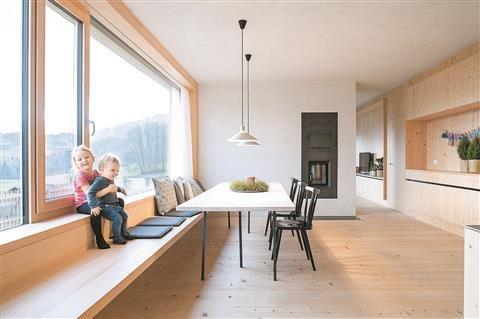 Großzügig – Essplatz mit Kochinsel rechts, langer Bank, robustem Fichtenboden und Ofenblock, der den Wohnraum abschirmt.