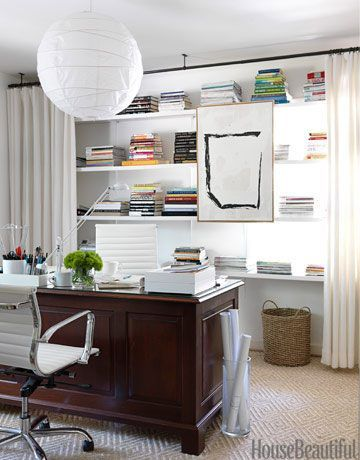Curtains soften the room and hide everyday office clutter on the shelves.