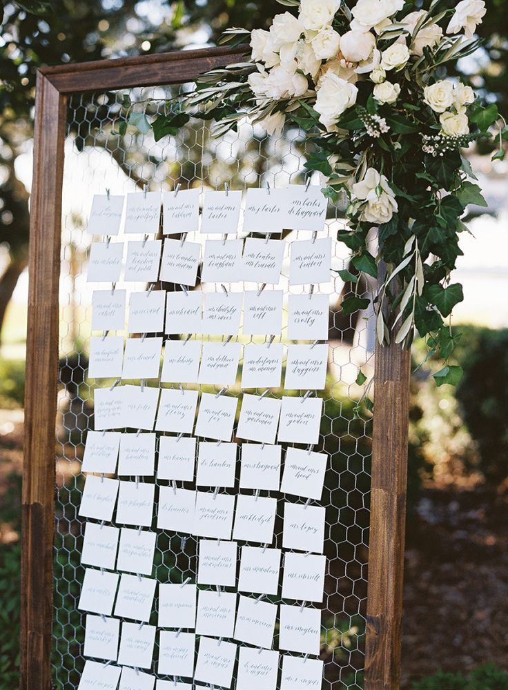 A charming idea for an escort card display; chicken wire suspended on a wooden frame.