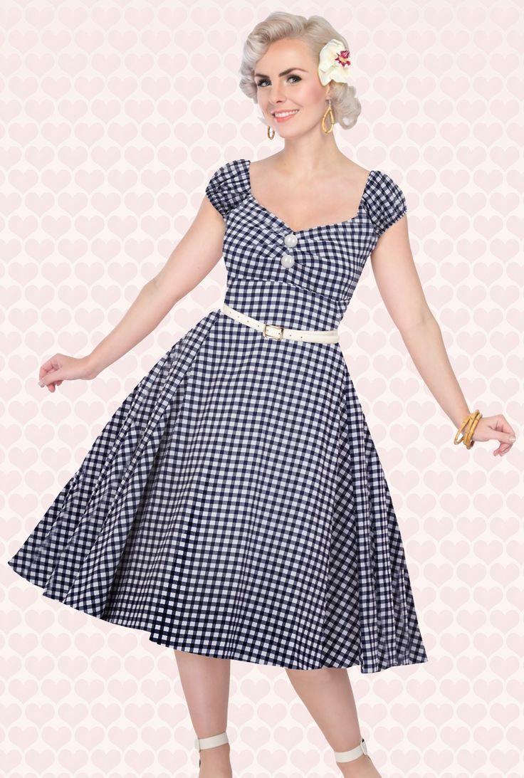 """De50s Dolores Doll Gingham Dress in Navy and Whitevan Collectif is eensuper vrouwelijke op de jaren 50 geïnspireerde jurk met het Brigitte Bardot ruitje!  Aansluitende Carmen style topmet schattige elastische pofmouwtjes die ook off-shoulder gedragen kunnen worden voor een meer romantische look ;)De top is geplooid bij de buste voor een mooi decolleté, heeft 2 """"faux"""" parelmoerachtige knopen en loopt vanaf de taille prachtig uit in een volle cirkelrok..."""
