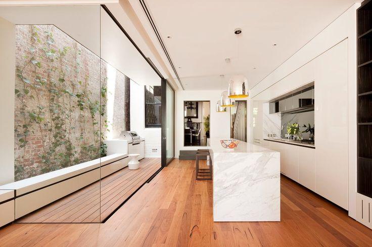 Cozinha com bancada em ilha de mármore, armários brancos, piso de madeira portas até o teto, e no corredor deck de madeira e churrasqueira. Dicas de Decoração paraChurrasqueira e Espaços Gourmet