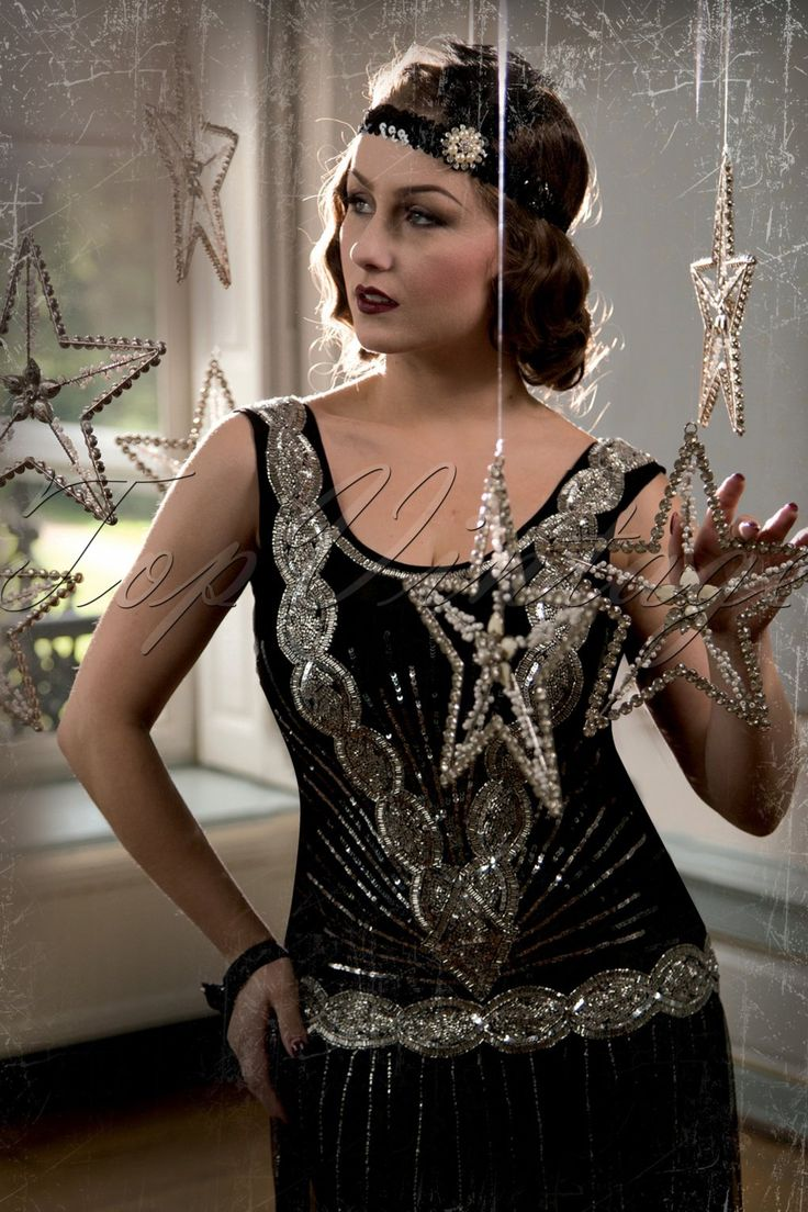 The20s Zelda Flapper Dress in Blackby Frock and Frill is a gorgeous Art-Deco inspired, 1920s flapper-style handmade reproduction, and the ideal cocktail dress.  A beautiful non-fitted style with an elegant scoop neckline, hand beaded with tiny shiny glass beads and silver sequins. The dress feautures a dropped waist and a deep V to the back with a horizontal strap, revealing a sexy triangular keyhole, oh la la! Finished off with a scalloped edge at the bottom and a hidden side zip...
