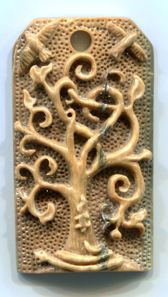 Deeply carved mammoth ivory pendant of Yggdrasil (Norse World Tree) - The serpent, Nidhogg, twine among its roots while the squirrel, Ratatoskr, fends it off. Above the tree the Odin's ravens, Huginn (Thought) and Munin (Memory, take flight over the world. 48 mm (2.875 in) tall, 26 mm (1 in wide), 8 mm (.3125 in) deep - sterling silver hanging ring supplied - hole 4.5 mm wide Yggdrasil World Tree Mammoth Ivory Pendant by dragonscalearts, $250.00