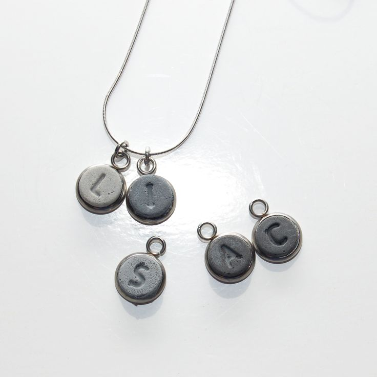 These concrete initial pendants are custom made Hanging from an 18 stainless steel snake chain and set in a stainless steel bezel Please indicate when purchasing the 2 initials and order that you would like them See other listings for 1 and 3 initial pendants Item will arrive in a metal tin