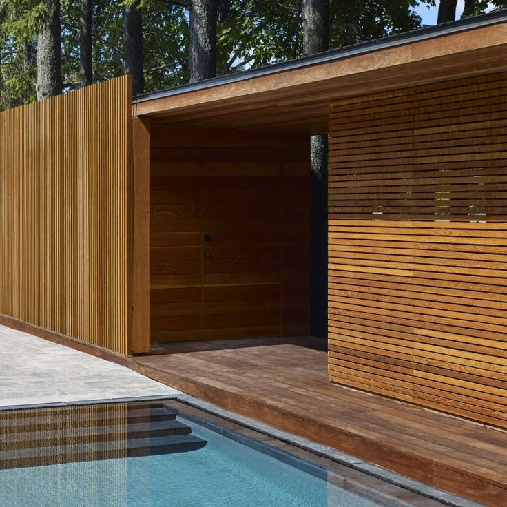 A veranda between the pool and the main house creates a shaded outdoor dining area over a bespoke oak table. The steel frame supports a slatted wooden roof that matches the pavilion.
