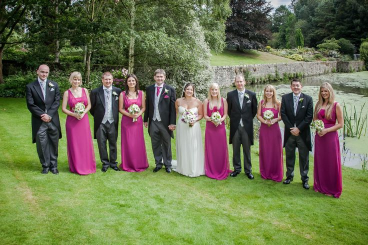 A group shot of the wedding party in front of the water at The Orangery.