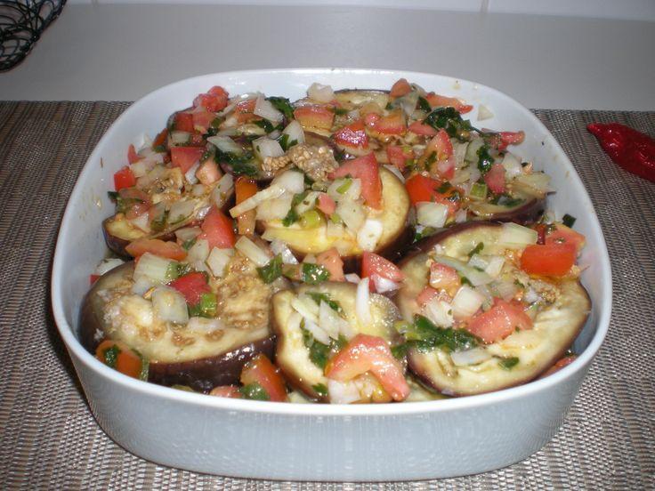 3 berinjelas médias  - 4 dentes de alho grandes  - 1 colher de sopa rasa de sal  - 2 colheres de sopa de azeite  - Para o vinagrete:  - 2 tomates maduros em cubinhos  - 1 cebola picadinha  - 1/2 xícara de vinagre  - Pimenta e sal a gosto  -