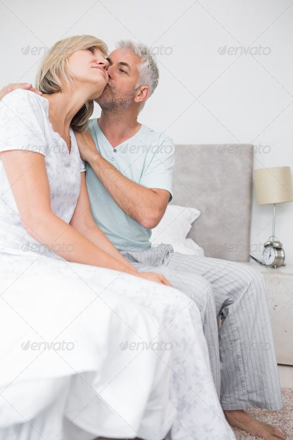 Side view of a mature man kissing womans cheek in bed at the home ...  50s, Domestic Life, bed, bedroom, care, casual, caucasian, cheek, couple, female, headboard, home, house, indoors, kissing, love, loving, male, man, mature adult, relationship, relaxation, romance, romantic, sitting, table lamp, together, woman