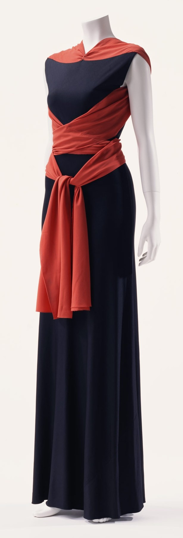 """Evening Dress, Madeleine Vionnet: ca. 1933, bias-cut rayon jersey, silk crepe sash. """"The dress was made of rayon jersey, treated in bias cut to fit around the body. The surrounding sash has the effect of highlighting the sleek body. The dress is from Madeleine Vionnet's personal wardrobe. The bias cut became a useful technique in the 1930s, when consciousness of body line was revived in fashion..."""""""