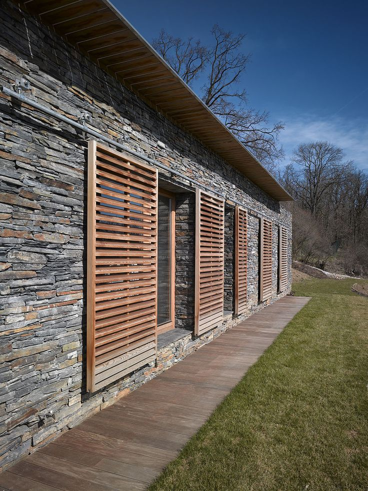 modern sliding wooden shutters over stone
