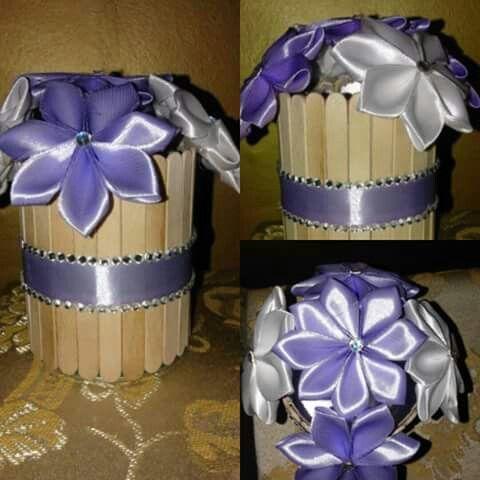Cestino di legno con fiori in raso viola e bianchi.