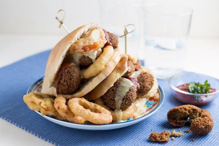 Panino con i falafel, anelli di cipolla e pomodori fritti
