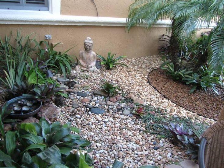 plantes à feuilles vert foncé, galets et statuette de Bouddha dans le jardin
