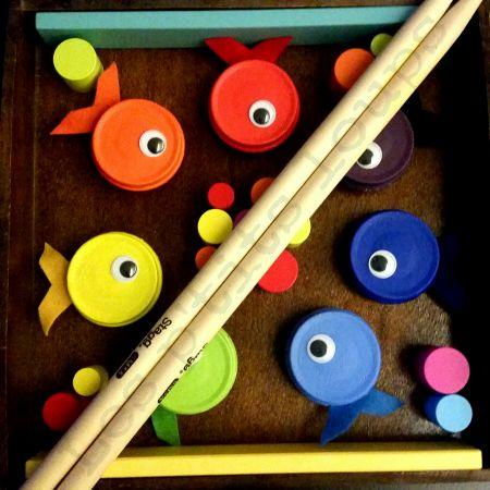 Matériel utilisé pour ce jeu de pêche : Pour les poissons - 14 bouchons de petits pots - enduit de préparation métal - peinture acrylique (rouge, orange, jaune, vert, bleu clair, bleu foncé et violet) - vernis mat - des yeux mobiles - de la feutrine de...