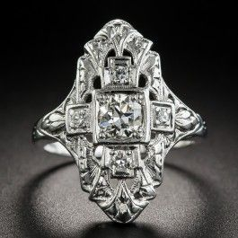 A striking geometric center is outlined by curvaceous foliate motifs in this 3/4 inch long and lovely original Art Deco dinner ring die-struck and hand finished in platinum, circa 1920s-30s. A central .32 carat European-cut diamond is accompanied by 4 small single-cut diamonds with hand engraved details and milgraining adding the finishing touches to this classic Jazz Age jewel. .40 carat total diamond weight. Currently ring size 4.