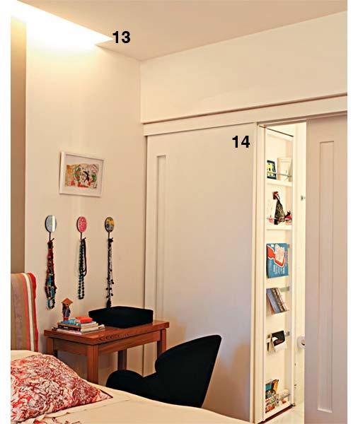 13. O rasgo de 20 cm de largura entre a parede da cabeceira e o rebaixo de gesso, no teto, embute a iluminação indireta e aconchegante. 14. A porta dupla, com acabamento de esmalte fosco branco, que liga o banheiro à suíte está presa a um trilho apenas na parte superior e tem puxadores discretos, cavados na marcenaria. Uma das folhas é versátil. Ela tanto fecha o banheiro como, se deslocada, esconde o armário de toalhas e roupas de cama no canto. Projeto de Renata Bartolomeu.