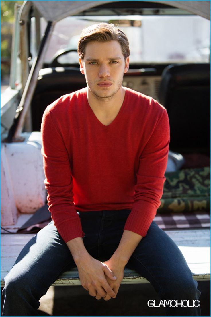 Dominic Sherwood wears a John Varvatos red v-neck sweater with Ted Baker denim…