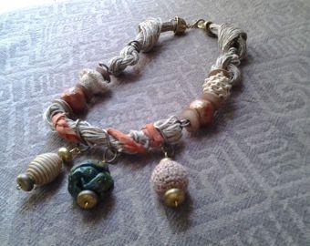 Collana fatta con fili di corda grezza, pelle arancione, charms, ciondoli di legno ricoperti di filo, ciondolo di cartapesta dipinto in verde.