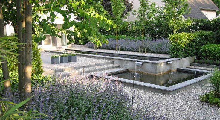 Rodenburg Tuinen: sierlijke tuin met spiegelvijver met niveauverschillen. Een ruime tuin met een sierlijke uitstraling door het gebruik van oud hollandse tegels, grind en een mooie verbinding met de beplanting.