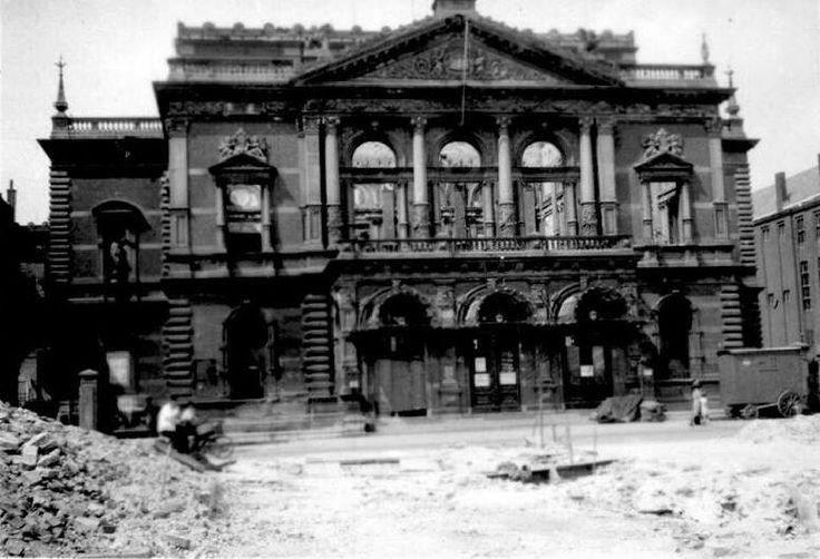 Gezicht op de door het Duitse bombardement van 14 mei 1940 getroffen grote schouwburg aan de Aert van Nesstraat. De muren staan nog overeind, maar je kijkt dwars door het pand heen.  In 1887 werd de Groote Schouwburg aan de Aert van Nesstraat geopend, een weelderig neoclassicistisch gebouw met salons en 1250 zitplaatsen