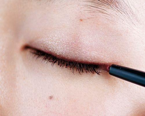 1.上まぶたに赤ラインを。目頭から目尻まで目の際に沿って、目尻はその延長線上に弧を描いて長めに引く。