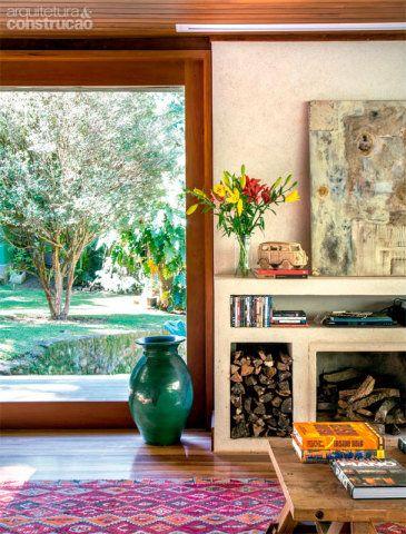 Painéis de vidro de 2,15 x 2,60 m, com esquadrias de garapa (execução da Set & Arte), envolvem toda a área social. A lareira, moldada com alvenaria, foi revestida de textura feita na obra, com massa de areia