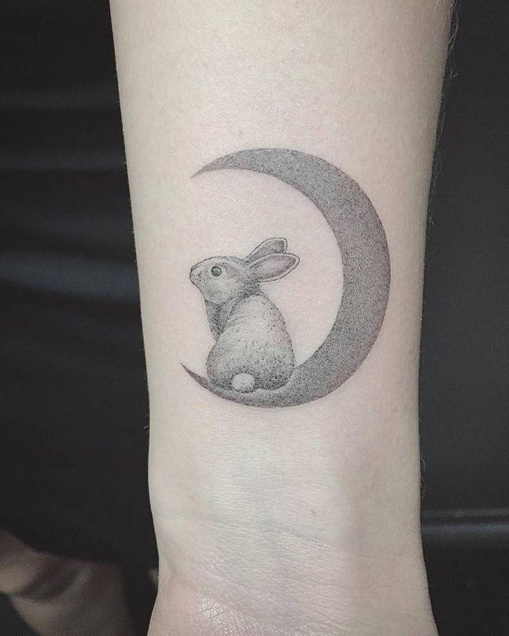 Tatuaje de estilo fine line de un conejo sobre la luna, situado en la muñeca. Artista tatuador: East