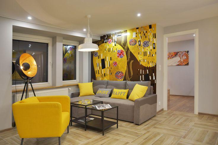 Dwupokojowe mieszkanie przy ul. Uniwersyteckiej, idealne pod wynajem dla singla lub pary. Wewnątrz dominuje jasna, nietuzinkowa kolorystyka. Neutralne biele  i ponadczasowe szarości zostały tu przełamane energetycznym żółtym akcentem, który nadaje aranżacji świeżego, radosnego charakteru i pięknie rozświetla przestrzeń. Ściany są ozdobione secesyjnymi ornamentami  i obrazami w stylu Klimta, które w zestawieniu z nowoczesnymi meblami  i dodatkami, tworzą modny, niebanalny look.