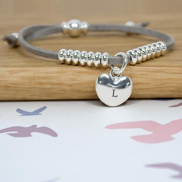 Perfect gift, modern bracelet made from coloured waxed cord and with curved silver plated heart. Can be personalised with up to three characters. Silver beads adorn the bracelet on either side of the heart as well as the clasp. Dimensions: 16cm (L) x 2cm (W).