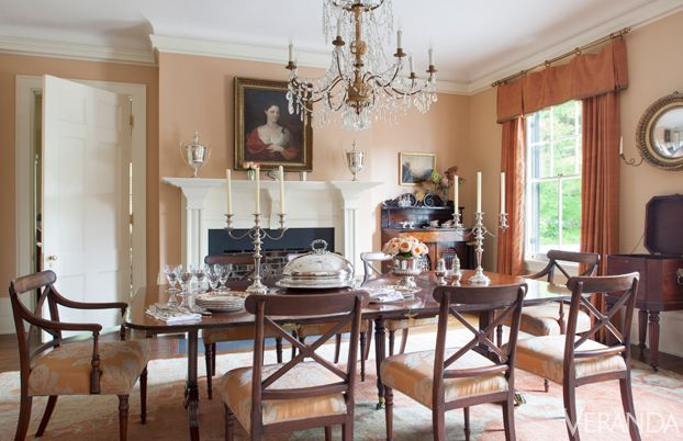 Salmon-colored walls in the dining room have a golden glow at night. 1820s mahogany dining table and chairs upholstered in Christopher Hyland silk-linen and Rose Tarlow linen trim. 19th-c. French crystal chandelier, Robuck & Co. Sterling urns, the Silver Vault of Charleston. Curtains in Lulan silk and Janet Yonaty silk trim. Walls in Farrow & Ball's Dutch Pink. Oushak rug.