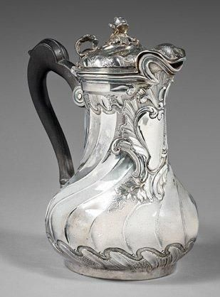 Marabout silver jug, the body decorated with a twisted rib smooth cartridge in a foliated rock around the lid (also twisted) to support inch perforated and spout stylized shell, the finial depicting a flower, shackle blackened wood. By Jean-Guillaume Véalle, Paris 1761.