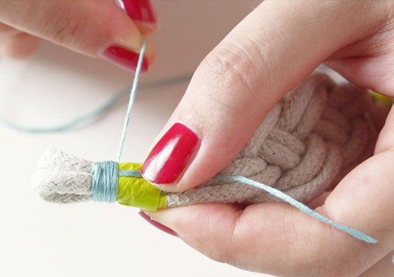 Para finalizar a pulseira, cubra a fita adesiva enrolada com linhas de bordar.