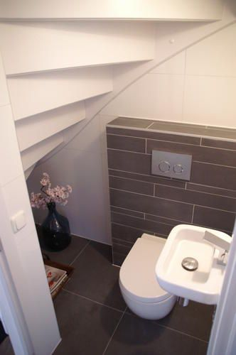 Tucked away under stairs a toilet. A great use of the space.<3